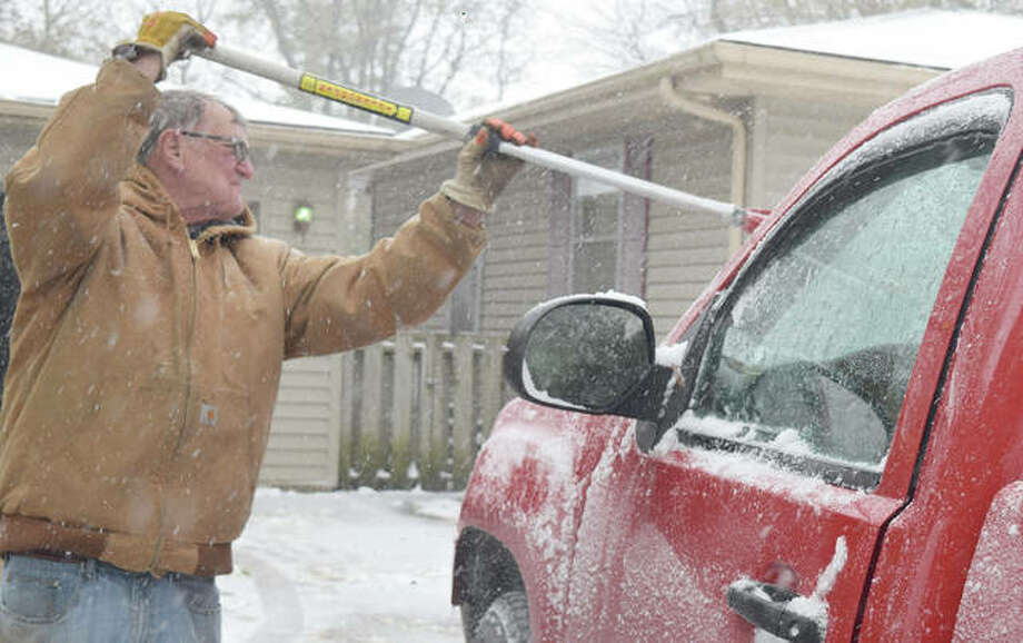 Mark Mefford of Jacksonville clears the windows of a truck Monday as snow continues to fall across west-central Illinois. Most of the region saw up to 2 inches of snow Monday, creating slippery conditions throughout the day. The largest accumulations were to the north, with some counties seeing 4 inches or more. The heaviest snow was reported in east-central Illinois, where the National Weather Service said snow was falling at a rate of 1 inch an hour and visibility was reduced to as little as a quarter-mile at times. Although the snow was expected to be short-lived, it was being followed by unseasonably cold temperatures. Photo: Samantha McDaniel-Ogletree | Journal-Courier