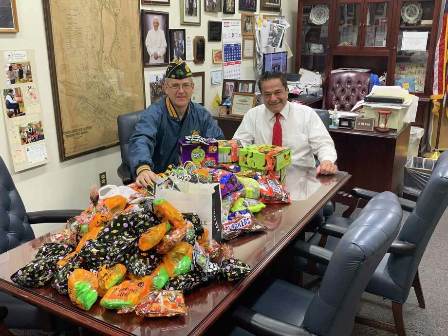 Pat Henri, a former Ansonia alderman, U.S. Navy veteran and member of Gordon-Visselli American Legion Post 50 and Ansonia Mayor David Cassetti sit with some of the 45 pounds of post-Halloween candy donated by residents. The candy will be taken to the VA Connecticut Healthcare System in West Haven. Photo: / Michael P. Mayko