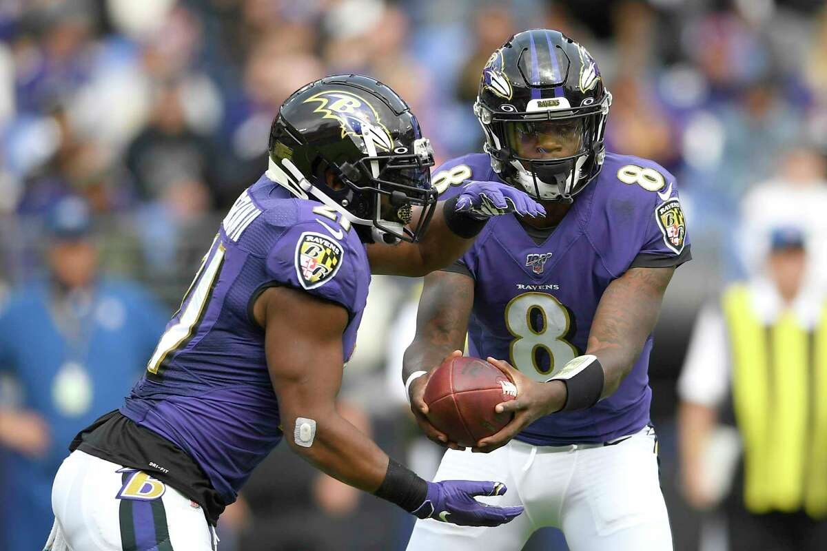 Baltimore Ravens quarterback Lamar Jackson (8) hands off to running back Mark Ingram (21) during the first half of a NFL football game against the Cincinnati Bengals Sunday, Oct. 13, 2019, in Baltimore. (AP Photo/Nick Wass)