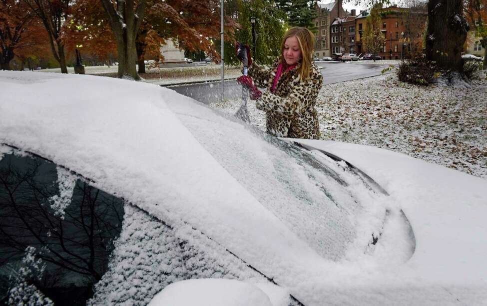 Elizabeth Murad of Albany cleans snow and ice off of her car on Tuesday, Nov. 12, 2019, in Albany, N.Y. (Paul Buckowski/Times Union)