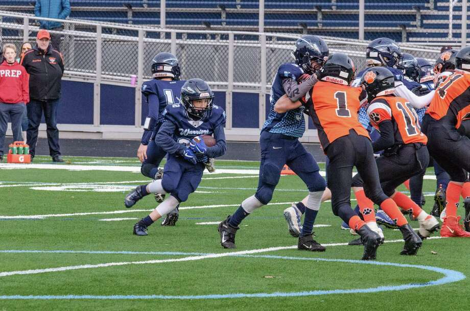 Jack Schwartz runs behind his offensive line during the Wilton seventh grade team's playoff win last weekend. Photo: Contributed Photo / Wilton Youth Football