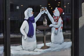 Downtown Midland has transformed into a winter wonderland with unified window paintings displayed on many of the storefronts and businesses along Main Street. Painted by a group called Brush Monkeys out of Ann Arbor, the paintings show whimsical wreaths and cheerful snowmen each with a personalized spin. (Ashley Schafer/Ashley.Schafer@hearstnp.com)