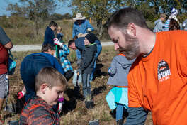 "Some 150 volunteers of all ages came out to the Katy Prairie Conservancy's Indiangrass Preserve to transplant native prairie plants to help restore the coastal prairie west of Houston during ""Putting Down Roots."""