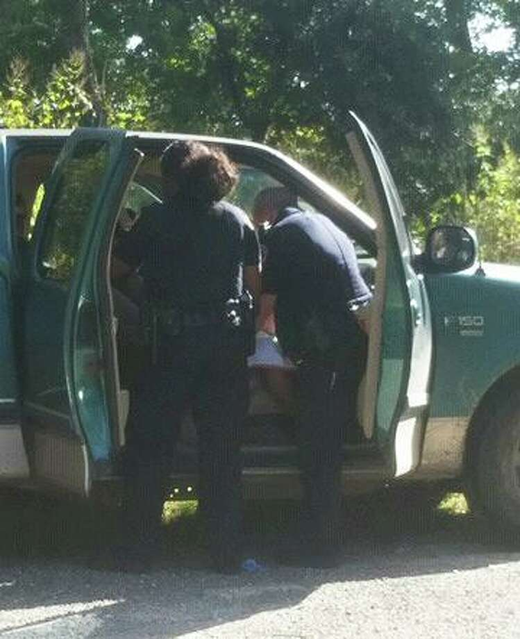 Officers huddle around the pickup where officer David Meyers helped deliver Kelly Major's baby. Photo: Submitted