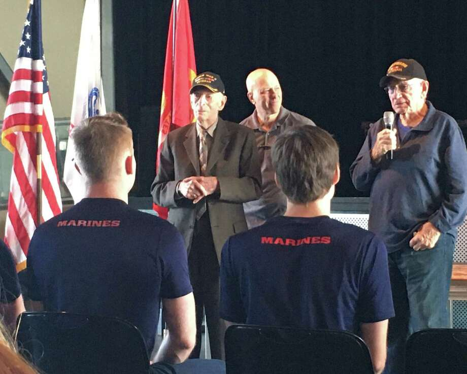 In the caps are World War II veterans Joseph Colwell and L.E. Millholland sharing advice with military recruits at the Nov. 10 Texans Embracing America's Military send-off. Between the veterans is Ralph Oliver, founder of TEAM Send-off Katy. Photo: Karen Zurawski