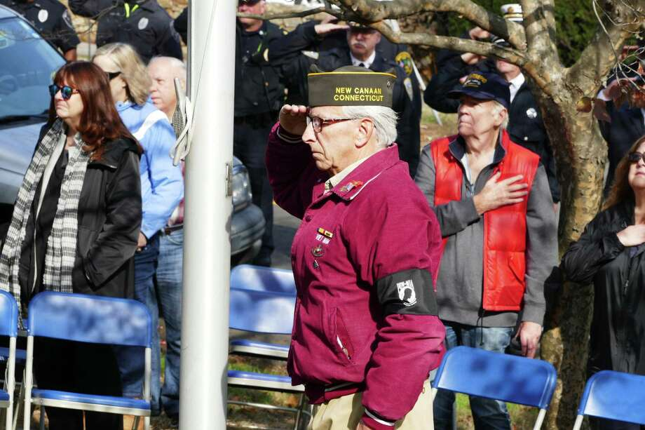 Vietnam Marine veteran Brian vanderHeyden saluted after lowering the flag to half staff on God's Acre at the Veterans Day ceremony. Photo: Grace Duffield / Hearst Connecticut Media