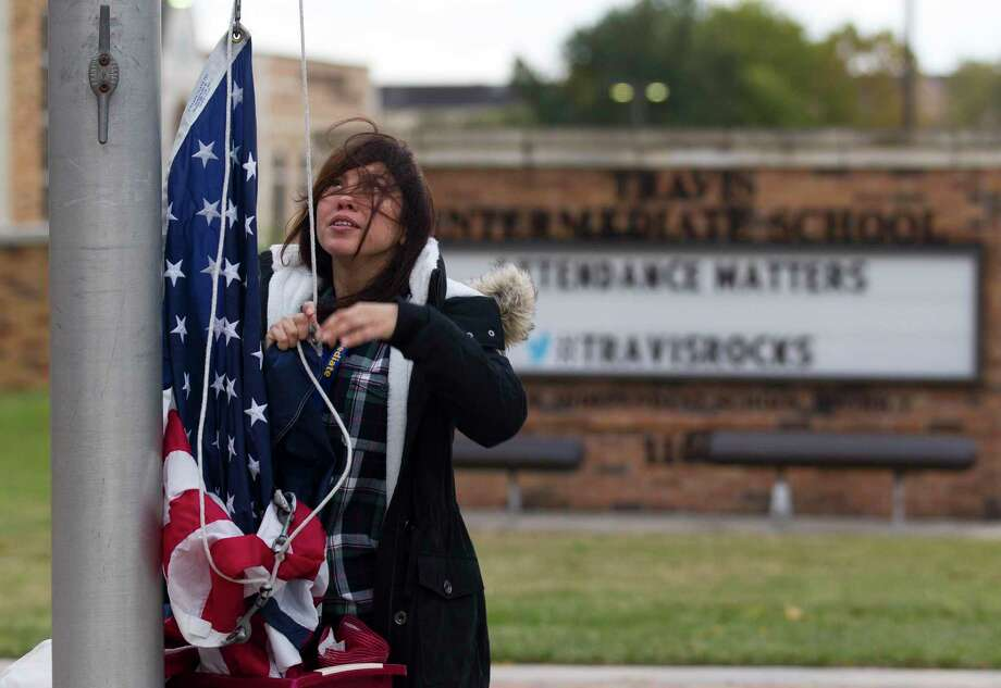 Despite windblown hair and 30-degree weather, custodian Loany Mendez raises the flags in front of Travis Intermediate School before the start of the school day, Tuesday, Nov. 12, 2019, in Conroe. Lows are expected in the 30 through the rest of the week with highs creeping into the 60s by Sunday. Photo: Jason Fochtman, Houston Chronicle / Staff Photographer / Houston Chronicle
