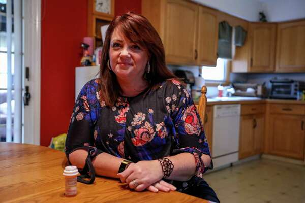 Heather Weise, 50, in her Milford home. While getting ready for work Weise says she takes morphine to help quell the pain she feels from adhesive arachnoiditis.