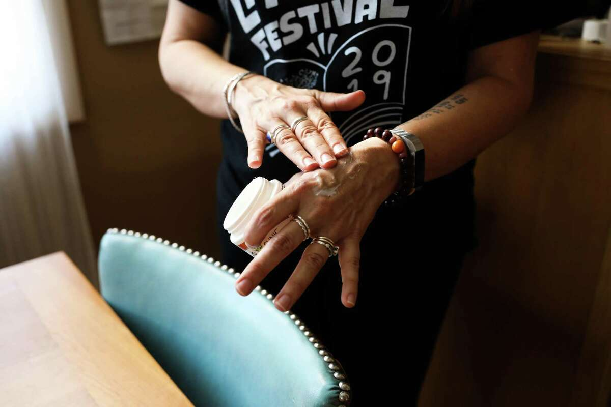 Sonya Huber applies CBD oil onto her hands. It is a daily routine for her in managing pain from rheumatoid arthritis.