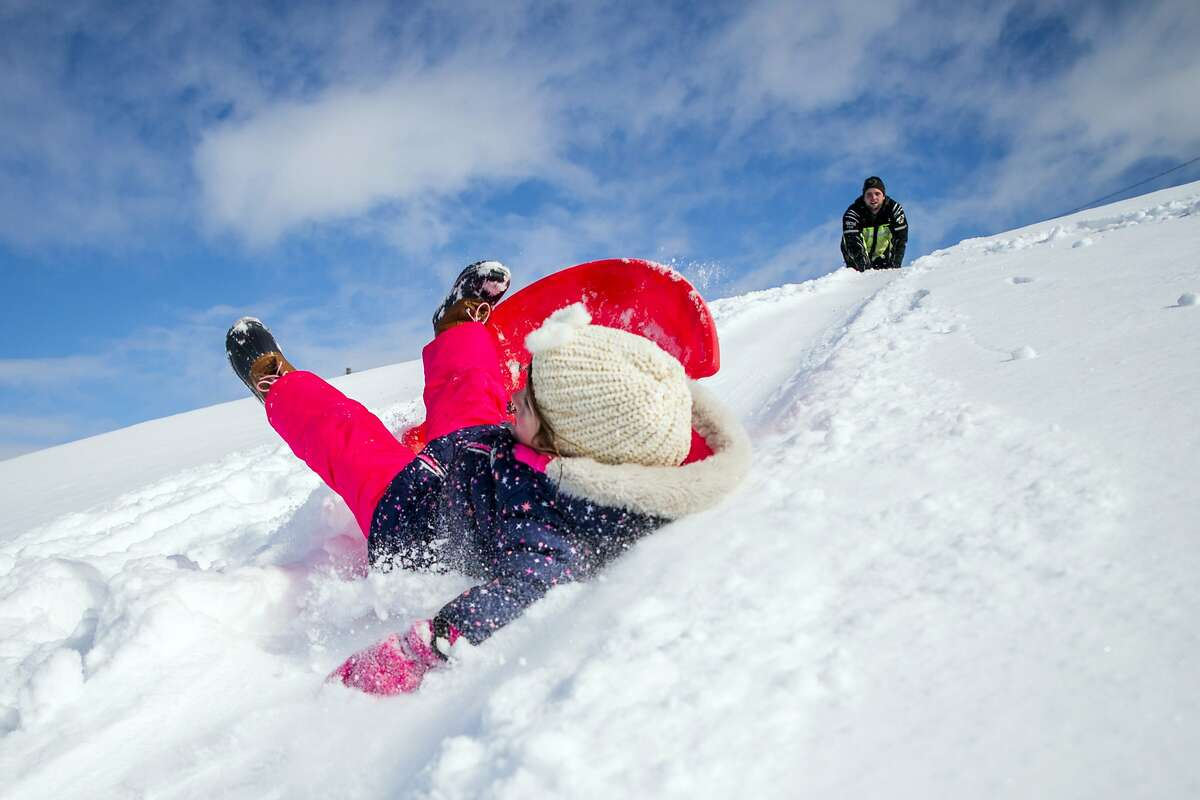 Emma Hart, 5, wipes out halfway down the hill after her father Ryan Hart, gave her a push while the two enjoy a day of sledding behind Southwestern Classical Academy on Tuesday, Nov. 12, 2019 in Flint, Mich. (Jake May/The Flint Journal via AP)