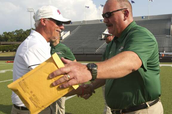The Woodlands head coach Jim Rapp, right, greets Oak Ridge head coach Mark Schmid before a District 15-6A high school football game at Buddy Moorhead Stadium, Friday, Sept. 13, 2019, in Conroe. Schmid, the former head coach for The Woodlands, coach alongside Rapp for nearly three decades.