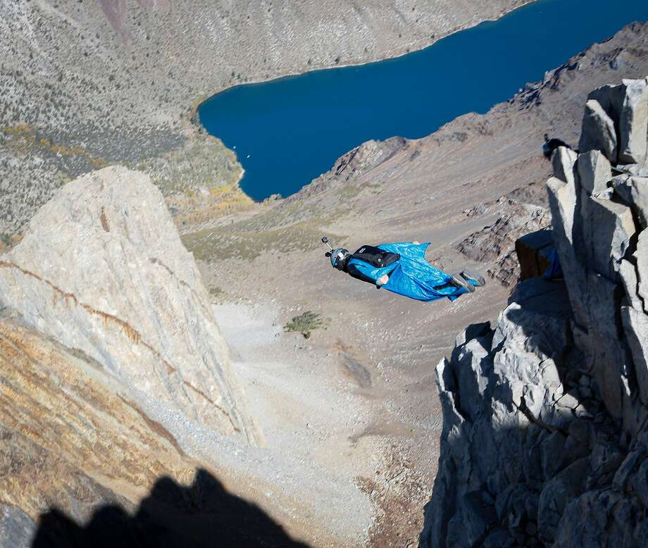 Daniel Ristow jumps from an exit point on Mount Morrison in order to execute a wingsuit base jump on Friday, Oct. 11, 2019 near Convict Lake, which is visible in the background. Photo: Greg Thomas / The Chronicle