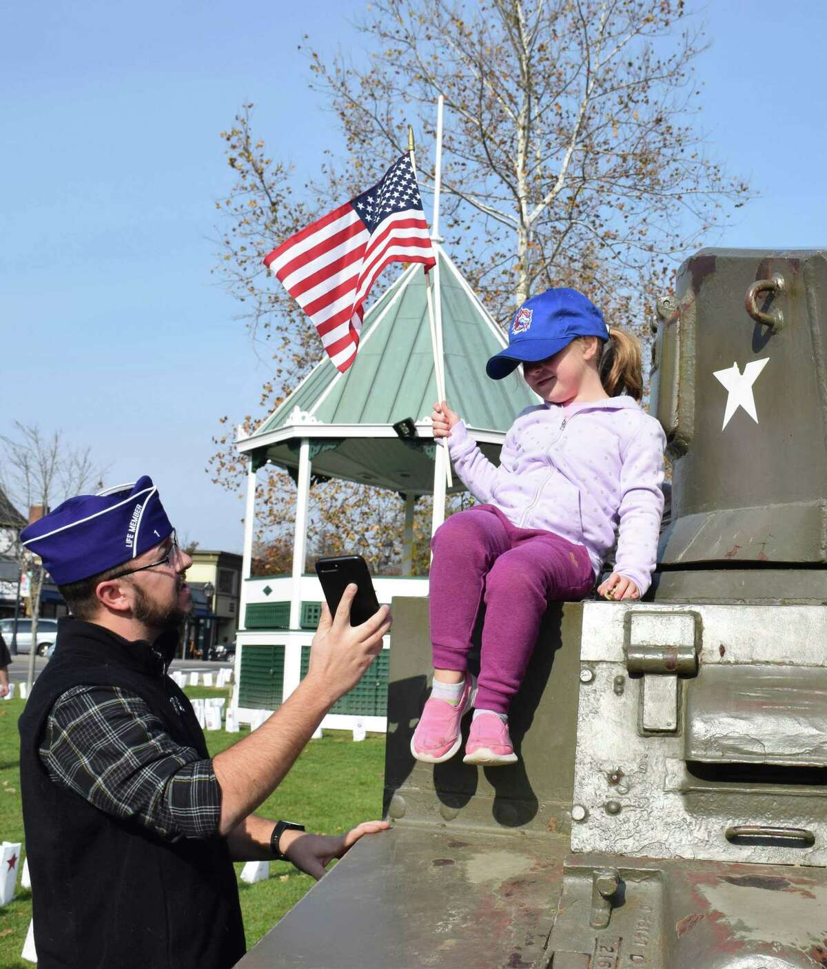 Veteran Matthew Hayes shows his daughter, Eliza, 4, the photo he took of her atop the tank on the Green before the ceremony.