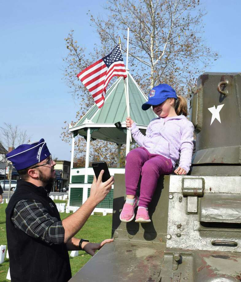 Veteran Matthew Hayes shows his daughter, Eliza, 4, the photo he took of her atop the tank on the Green before the ceremony. Photo: Deborah Rose / Hearst Connecticut Media / The News-Times  / Spectrum