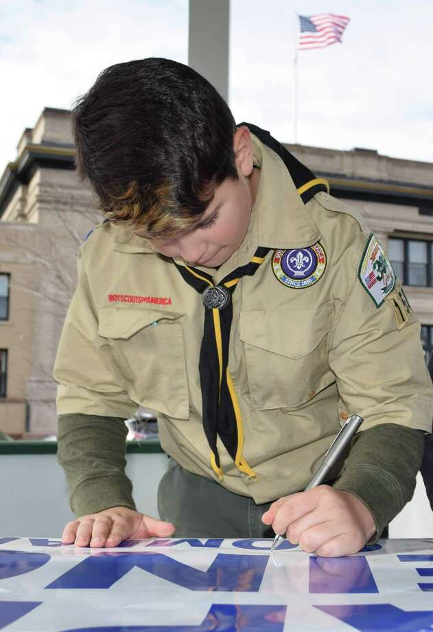 Boy Scout Brett Perrenod signs the welcome home banner for the Marines. Photo: Deborah Rose / Hearst Connecticut Media / The News-Times  / Spectrum
