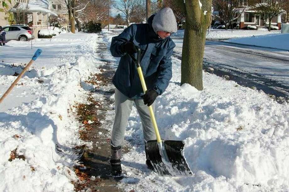 Garett Taylor, 14, helps his mom shovel snow on snow day. (Sara Eisinger/Huron Daily Tribune)