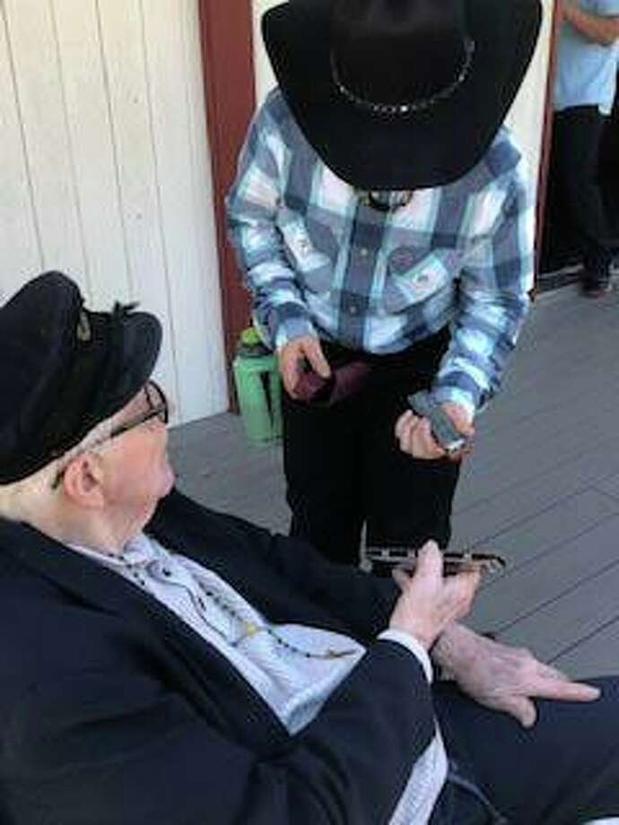 Candlewood Valley Health and Rehabilitation resident Carl Heinemeyer, who carries a harmonica in his pocket, and student Hunter W. discuss their harmonicas before leading those gathered in song. Photo: Courtesy Of Glenholme School / The News-Times Contributed