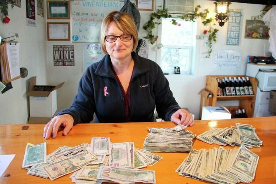 Linda Gucwa with $800 at Vine-N-Berry's tasting room. Gucwa plans on donating the money to St. Jude's. (Robert Creenan/Huron Daily Tribune)