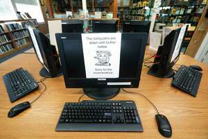 Signs on a bank of computers tell visitors that the machines are not working at the public library in Wilmer, Texas, Thursday, Aug. 22, 2019. Cyberattacks that recently crippled nearly two dozen Texas cities have put other local governments on guard. (AP Photo/Tony Gutierrez)