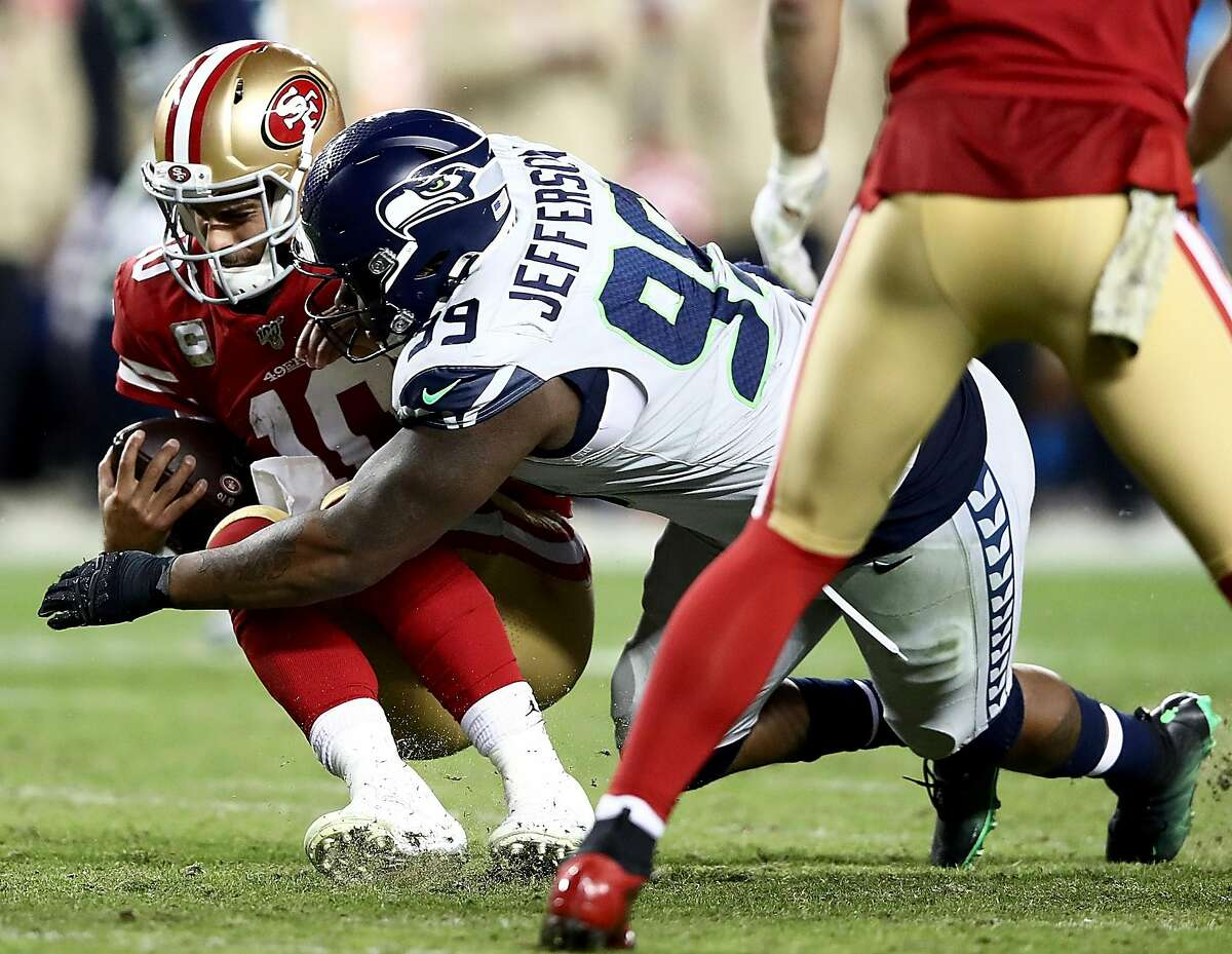 SANTA CLARA, CALIFORNIA - NOVEMBER 11: Quarterback Jimmy Garoppolo #10 of the San Francisco 49ers is sacked by defensive tackle Quinton Jefferson #99 of the Seattle Seahawks in the game at Levi's Stadium on November 11, 2019 in Santa Clara, California. (Photo by Ezra Shaw/Getty Images)