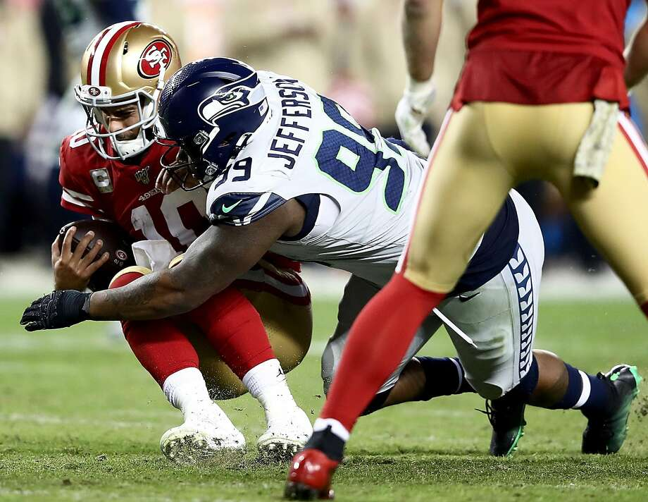 SANTA CLARA, CALIFORNIA - NOVEMBER 11: Quarterback Jimmy Garoppolo #10 of the San Francisco 49ers is sacked by defensive tackle Quinton Jefferson #99 of the Seattle Seahawks in the game at Levi's Stadium on November 11, 2019 in Santa Clara, California. (Photo by Ezra Shaw/Getty Images) Photo: Ezra Shaw / Getty Images