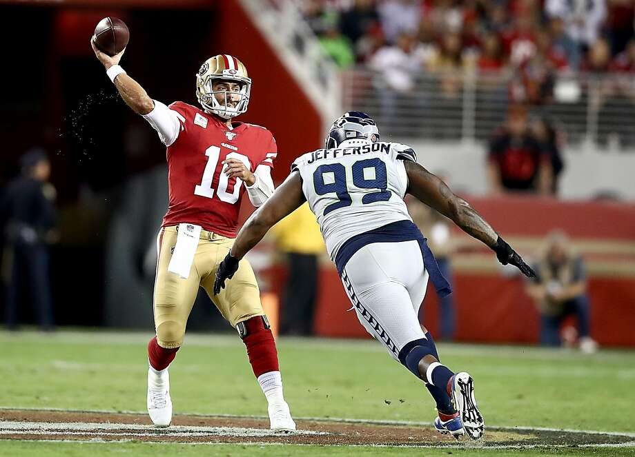 SANTA CLARA, CALIFORNIA - NOVEMBER 11: Quarterback Jimmy Garoppolo #10 of the San Francisco 49ers delivers a pass over the defense of defensive tackle Quinton Jefferson #99 of the Seattle Seahawks  at Levi's Stadium on November 11, 2019 in Santa Clara, California. (Photo by Ezra Shaw/Getty Images) Photo: Ezra Shaw / Getty Images