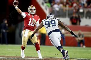 SANTA CLARA, CALIFORNIA - NOVEMBER 11: Quarterback Jimmy Garoppolo #10 of the San Francisco 49ers delivers a pass over the defense of defensive tackle Quinton Jefferson #99 of the Seattle Seahawks  at Levi's Stadium on November 11, 2019 in Santa Clara, California. (Photo by Ezra Shaw/Getty Images)
