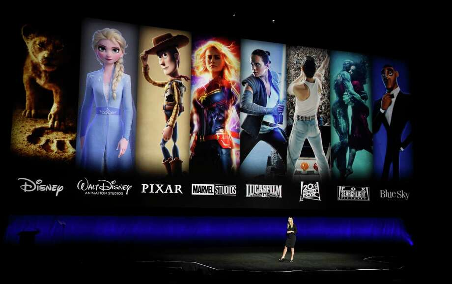 FILE - In this April 3, 2019, file photo characters from Disney and Fox movies are displayed behind Cathleen Taff, president of distribution, franchise management, business and audience insight for Walt Disney Studios during the Walt Disney Studios Motion Pictures presentation at CinemaCon 2019, the official convention of the National Association of Theatre Owners (NATO) at Caesars Palace in Las Vegas. On Tuesday, Nov. 12, Disney Plus launches its streaming service. (Photo by Chris Pizzello/Invision/AP, File) Photo: Chris Pizzello / 2019 Invision