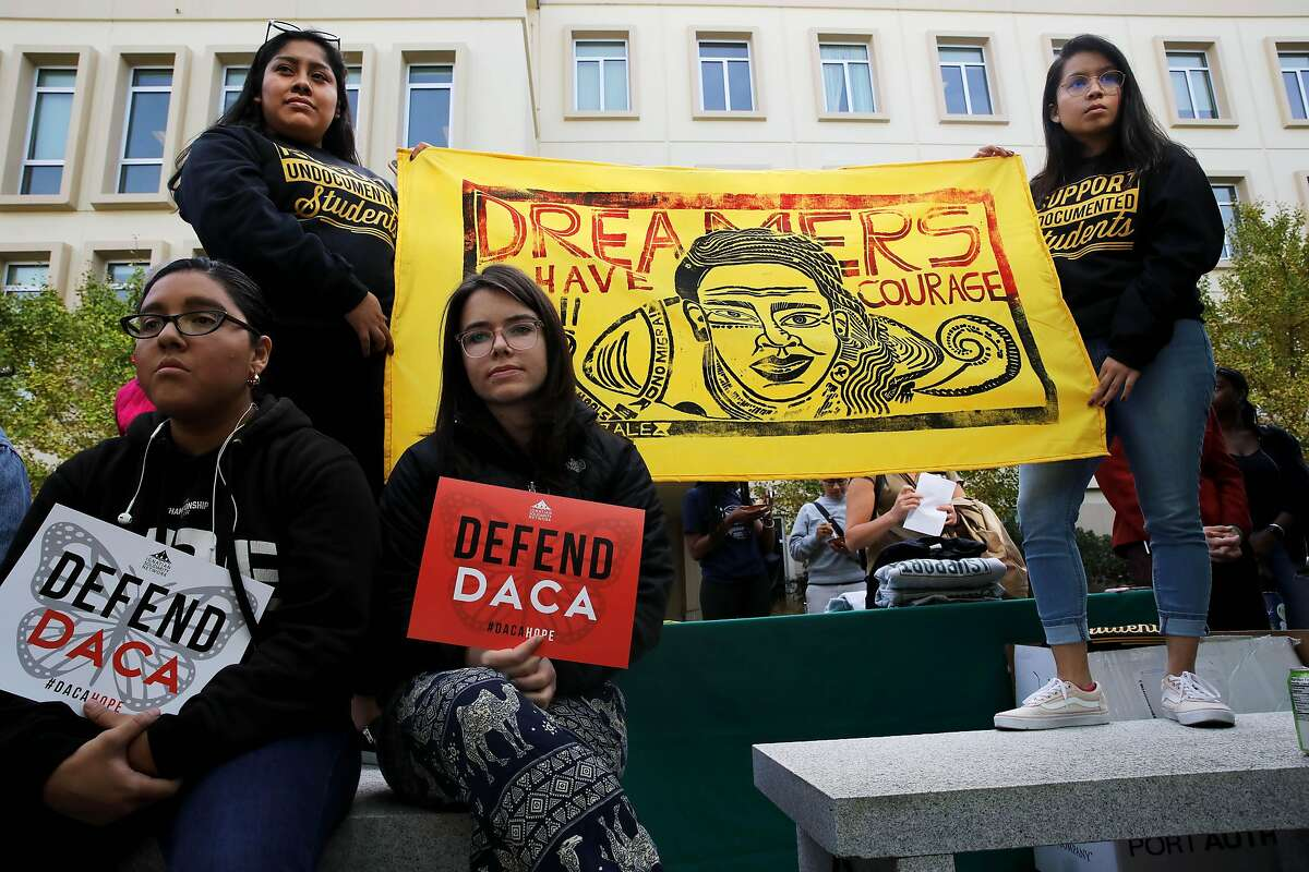 """Kiana Martinez, left, and Mariah O'Grady, hold """"Defend DACA"""" signs as they sit in front of Gladys Perez, left, Office of Diversity Engagement and Community Outreach, at the University of San Francisco, and Diana Elizabeth Garcia Rodriguez, a Higher Education and Student Affairs Masters student, right, hold a """"Dreamers Have Courage"""" banner at the University of San Francisco during a vigil and teach-in protest, coinciding with other protests against the Trump administration's attempts to dismantle the DACA program, in San Francisco, Calif., on Tuesday, November 12, 2019. On Tuesday, the Supreme Court heard oral arguments regarding whether or not former President Barack Obama overstepped his legal authority when he created the DACA program during his tenure. The Trump administration maintains the program has introduced thousands of people into American society who have become criminals, while proponents point to the many thousands who have grown up to become high-achieving, productive members of their communities."""