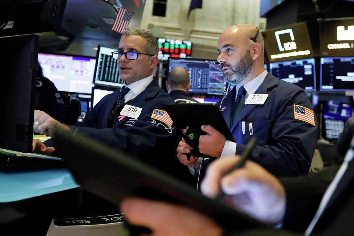 Specialist Anthony Rinaldi, left, and trader Fred DeMarco work on the floor of the New York Stock Exchange, Tuesday, Nov. 12, 2019. Stocks are opening slightly higher on Wall Street, led by gains in technology and health care companies. (AP Photo/Richard Drew)