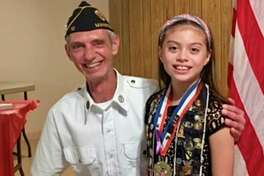 American Legion Post No. 10 Commander Brian Kluesner stands with Miss Sawyer Hendrickson on Sunday during the post's annual Veterans Day Dinner. (Photo provided by Sandy Pelarski)