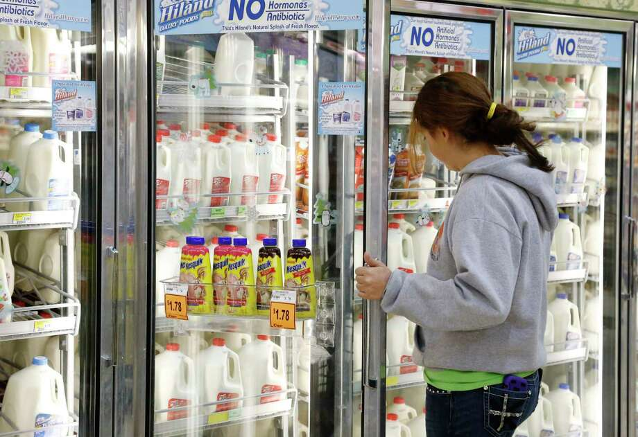 FILE - In this Dec. 4, 2013, file photo Jessica Walton, of Guthrie, Okla., reaches for a container of milk at a grocery store in Edmond, Okla. On Tuesday, Nov. 12, 2019, Dean Foods, the nation's largest milk processor, filed for Chapter 11 bankruptcy protection and said it may sell the company off to the Dairy Farmers of America. (AP Photo/Sue Ogrocki, File) Photo: Sue Ogrocki / Copyright 2019 The Associated Press. All rights reserved.