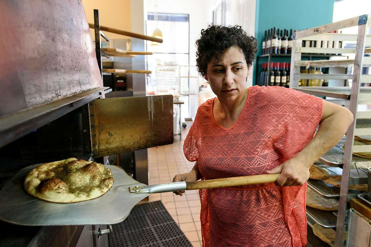 Owner Reem Assil pulls a Za'atar Man'oushe from the oven at Reem's in Oakland, Calif, on Wednesday, April 17, 2019.