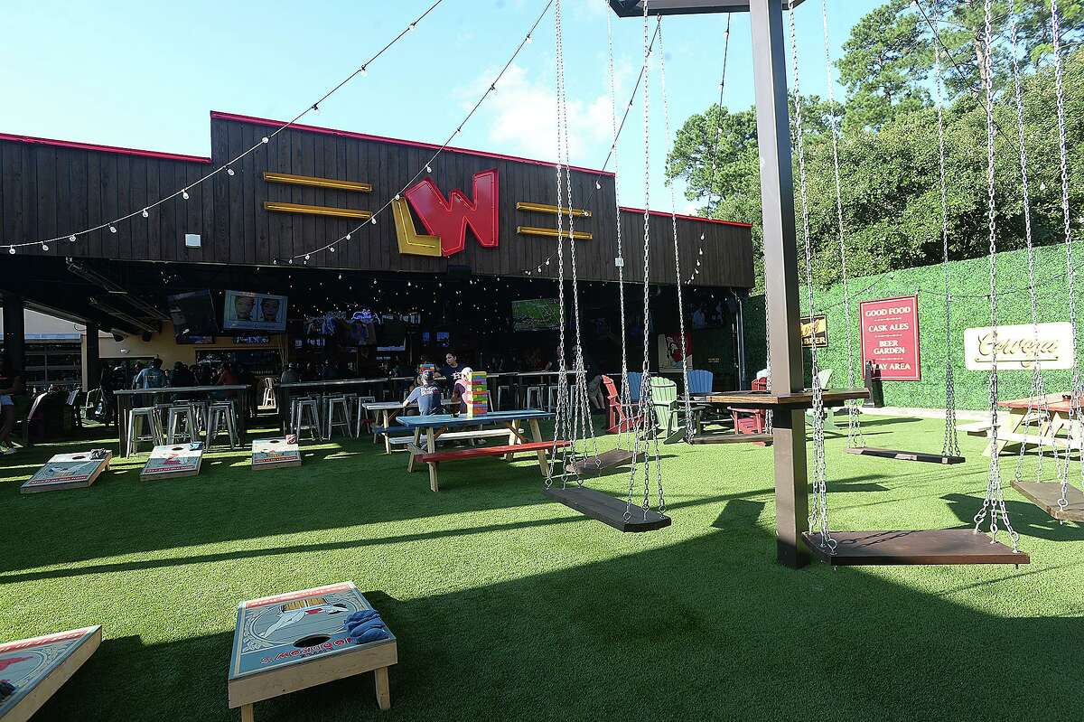 Customers socialize and enjoy the atmosphere at Little Woodrow's, which features an outdoor patio area with swings and games at one of Beaumont's newest establishments. Photo taken Thursday, July 18, 2019 Kim Brent/The Enterprise