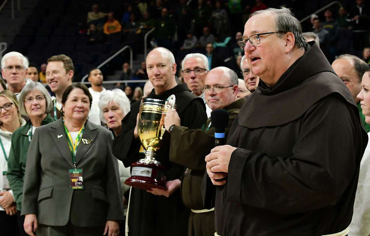 The Franciscan Cup is held during a pre-game ceremony at the Siena basketball game against St. Bonaventure at the Times Union Center on Tuesday, Nov. 12, 2019 in Albany, N.Y. Brother F. Edward Coughlin's family came on the court and Father Kevin Mullen, right, whom Coughlin replaced at Siena, said a few words in his honor. (Lori Van Buren/Times Union)