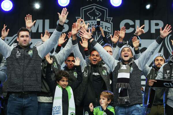Sounders players raise their hands to the crowd as the city celebrates the their MLS Cup Championship win with a parade from Westlake Park to Seattle Center and a rally, Tuesday, Nov. 12, 2019. The Sounders beat Toronto 3-1 to bring home their second MLS Cup in four years.
