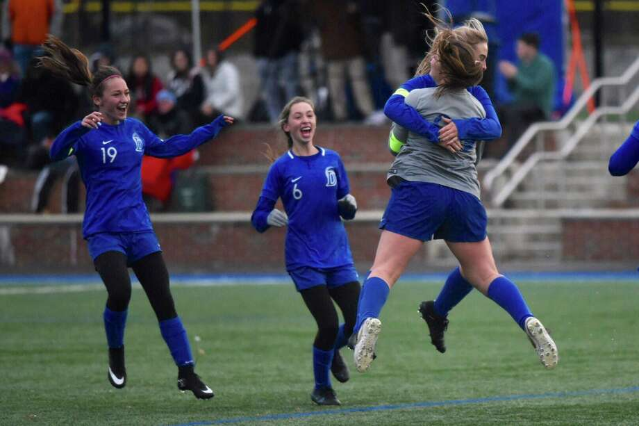The Darien girls soccer team, including Kate Bellissimo (19), Katharine Chandler (6), Nelle Kniffin and goalie Olivia Maniscalco, celebrates an overtime win against Hall in the CIAC Class LL first round at Darien High School on Tuesday, Nov. 12, 2019. Photo: Dave Stewart / Hearst Connecticut Media / Hearst Connecticut Meda