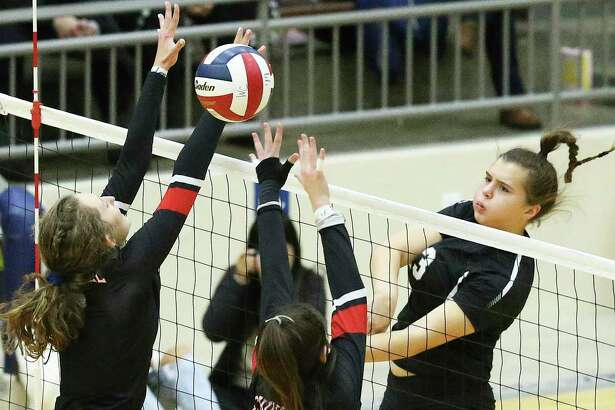 Clark hitter Mackenzie Wolff gets the ball over defenders as Clark plays Churchill in 6A third round volleyball playoff action at the Alamo Convocation Center on Nov. 12, 2019.