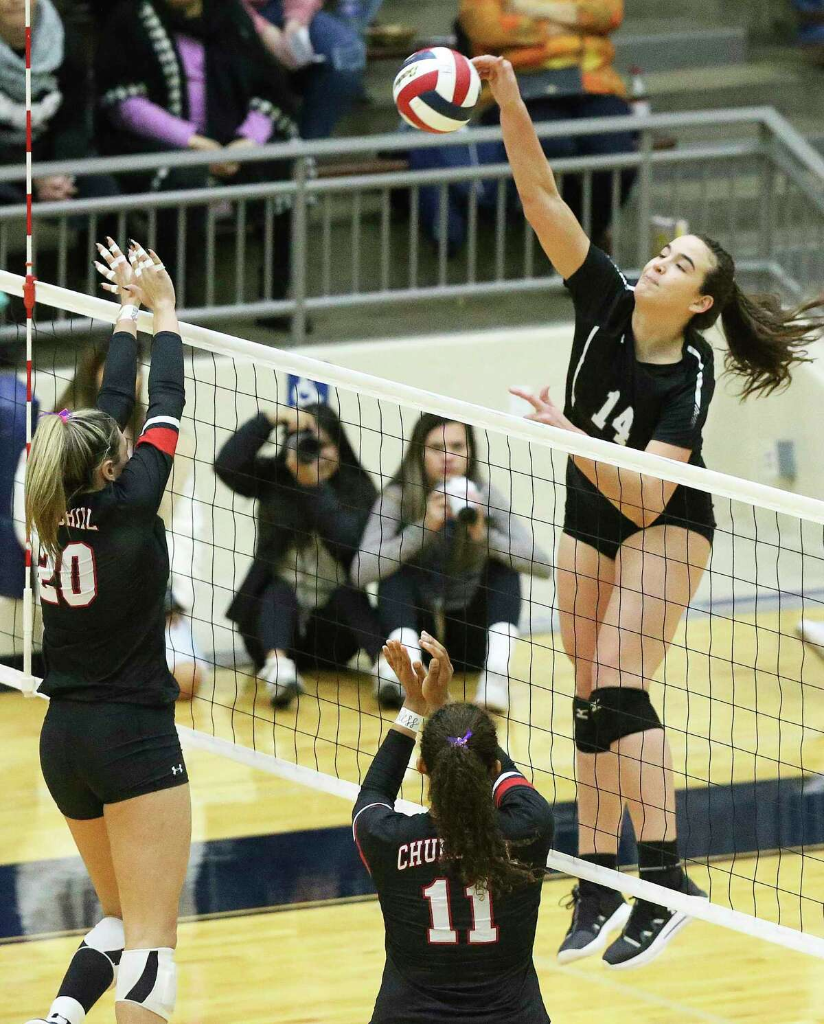 Elise McGhee slams a shot for the Cougars as Clark defeats Churchill in 6A third round volleyball playoff action at the Alamo Convocation Center on Nov. 12, 2019.