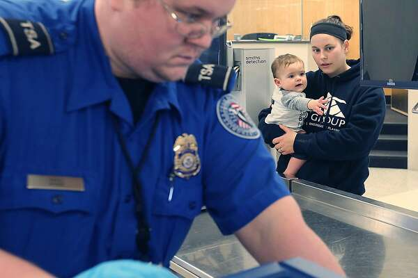 Akron-Canton Airport TSA Agent James Sakel checks a sippy cup belonging to Meghan Mason and her son Daulton, 1, of Norton, Ohio as they head through a security checkpoint in Green, Ohio. It is important to travel with family to see the world through a new perspective. (Phil Masturzo/Akron Beacon Journal/TNS)