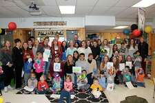 Corey Bechler's high school art class and Traci Kelly's kindergarten students pose for a group photo with their monsters. (Photo/Robert Myers)