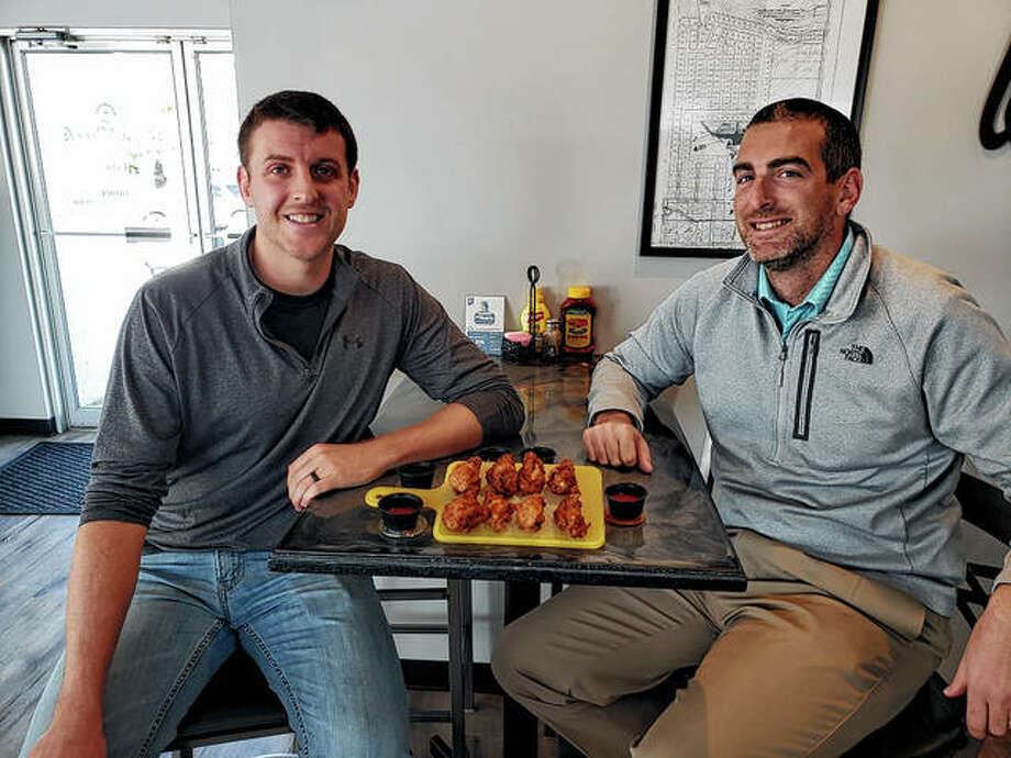 A plate of hot wings rests Tuesday between Ryne Turke (left) and John Rohn at K's Creek Golf Club as they talk about this weekend's Hot Ones Chicken Wing Charity Challenge at the club.