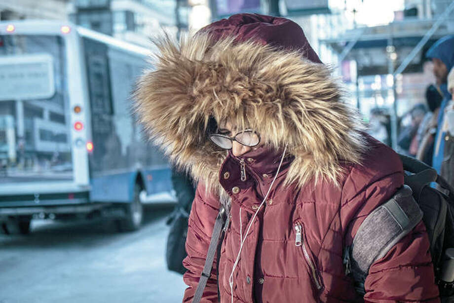 """A commuter waits for a bus Tuesday in Chicago. The National Weather Service said Tuesday and today may see record cold from the southern Plains to the Mississippi Valley to the Great Lakes and beyond, thanks to what it calls an """"Arctic airmass"""" that started in Siberia and has been spilling over a big chunk of the Midwest. Photo: Rich Hein 