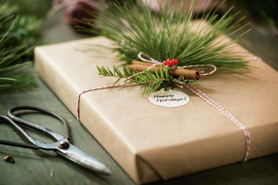 Christmas gift wrapped in brown kraft paper, decorated with a cinnamon stick and fresh greenery. Photo: Getty Images / 1MoreCreative / 1MoreCreative