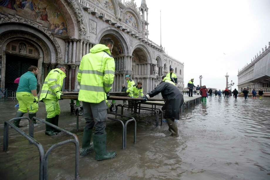 City council workers place catwalks in St. Mark's Square, in Venice, Wednesday, Nov. 13, 2019. The high-water mark hit 187 centimeters (74 inches) late Tuesday, Nov. 12, 2019, meaning more than 85% of the city was flooded. The highest level ever recorded was 194 centimeters (76 inches) during infamous flooding in 1966. Photo: Luca Bruno, AP / Copyright 2019 The Associated Press. All rights reserved.