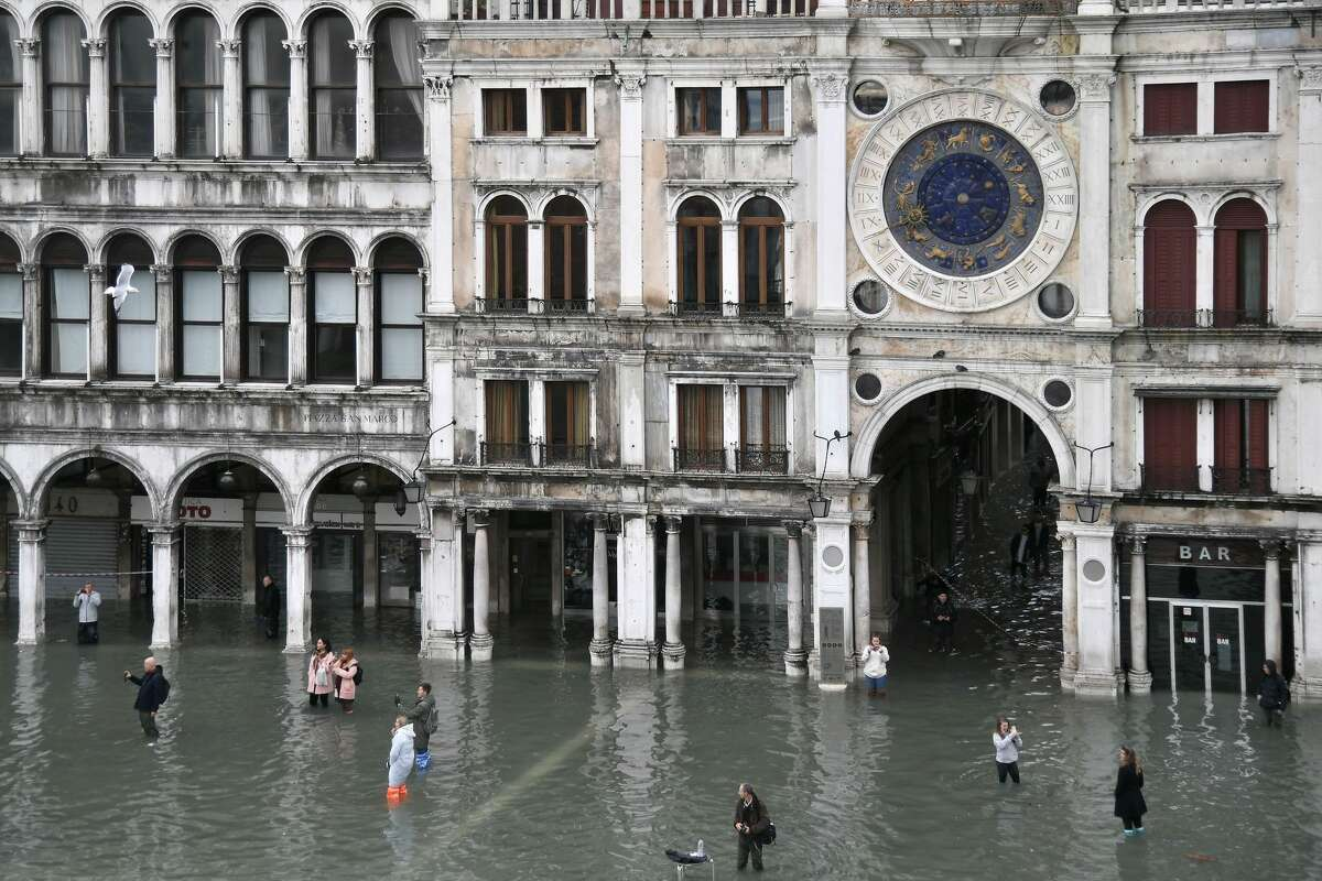 """People walk across and take photos at the flooded St. Mark's Square after an exceptional overnight """"Alta Acqua"""" high tide water level, on November 13, 2019 in Venice. - Venice was hit by the highest tide in more than 50 years late November 12, with tourists wading through flooded streets to seek shelter as a fierce wind whipped up waves in St. Mark's Square."""