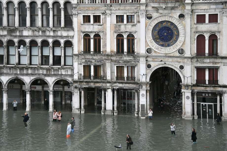 "People walk across and take photos at the flooded St. Mark's Square after an exceptional overnight ""Alta Acqua"" high tide water level, on November 13, 2019 in Venice. - Venice was hit by the highest tide in more than 50 years late November 12, with tourists wading through flooded streets to seek shelter as a fierce wind whipped up waves in St. Mark's Square. Photo: MARCO BERTORELLO/AFP Via Getty Images"