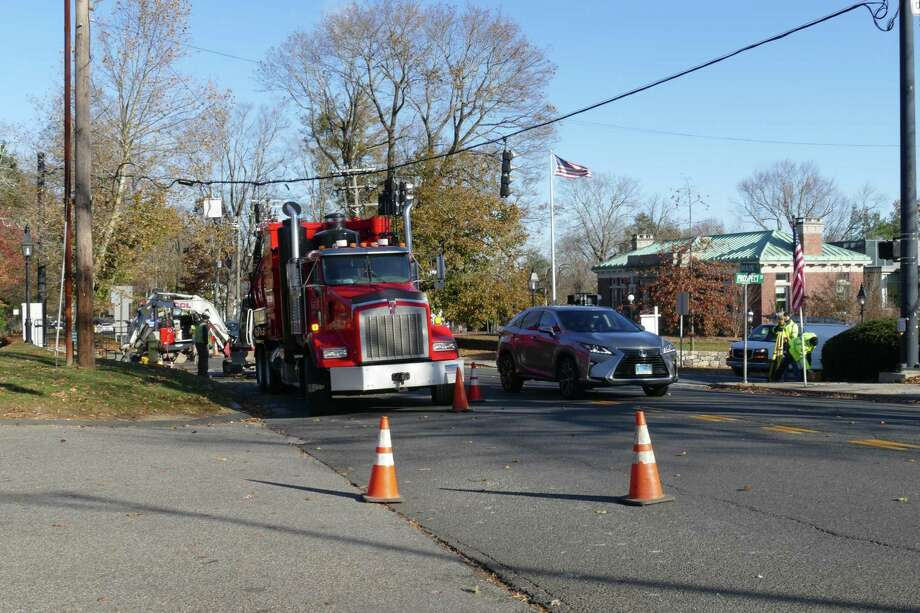 A car moves around a utility truck on Main Street Wednesday, Nov. 13. Photo: Stephen Coulter / Hearst Connecticut Media