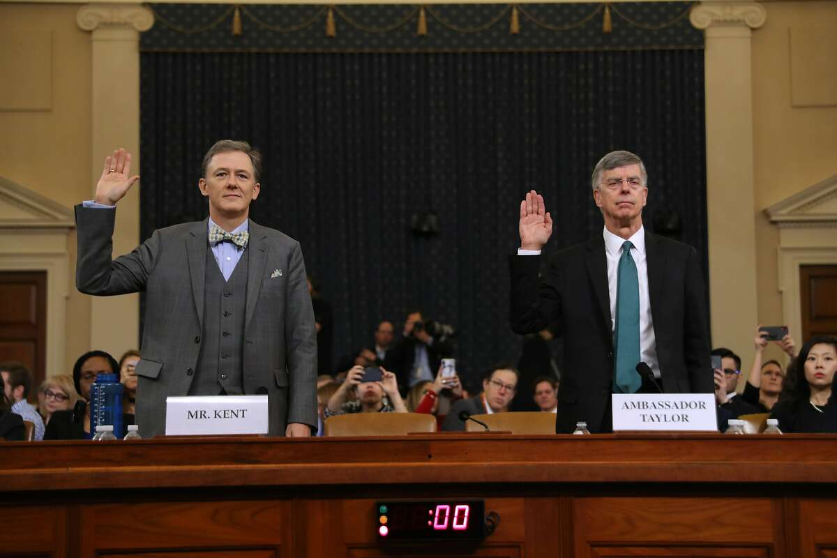 Trump public impeachment hearings Deputy Assistant Secretary for European and Eurasian Affairs George P. Kent (L) and top U.S. diplomat in Ukraine William B. Taylor Jr. are sworn in before testifying before the House Intelligence Committee in the Longworth House Office Building on Capitol Hill November 13, 2019 in Washington, DC. In the first public impeachment hearings in more than two decades, House Democrats are trying to build a case that President Donald Trump committed extortion, bribery or coercion by trying to enlist Ukraine to investigate his political rival in exchange for military aide and a White House meeting that Ukraine President Volodymyr Zelensky sought with Trump. (Photo by Chip Somodevilla/Getty Images)