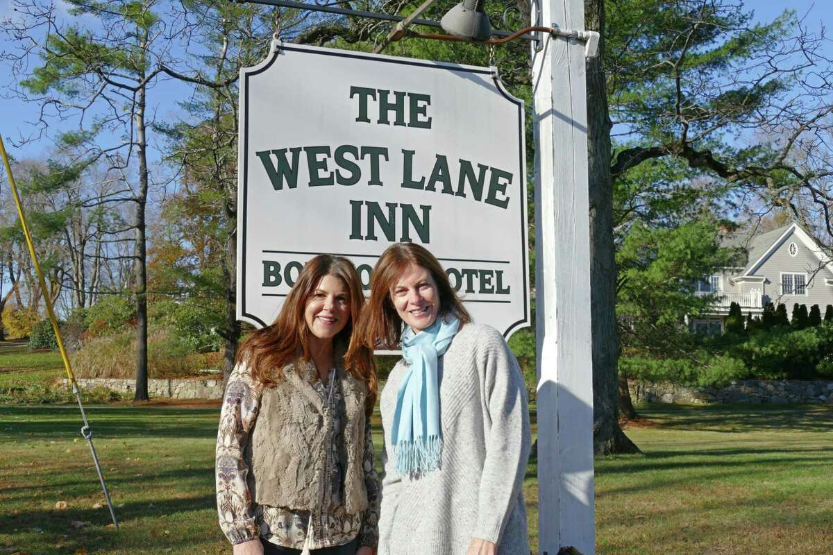 Danille Petrie and Christine Carnicelli, new owners of The West Lane Inn, stand in front of the boutique hotel's welcome sign.
